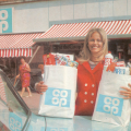 Woman in a red coat holding co-op bags, circa 1968