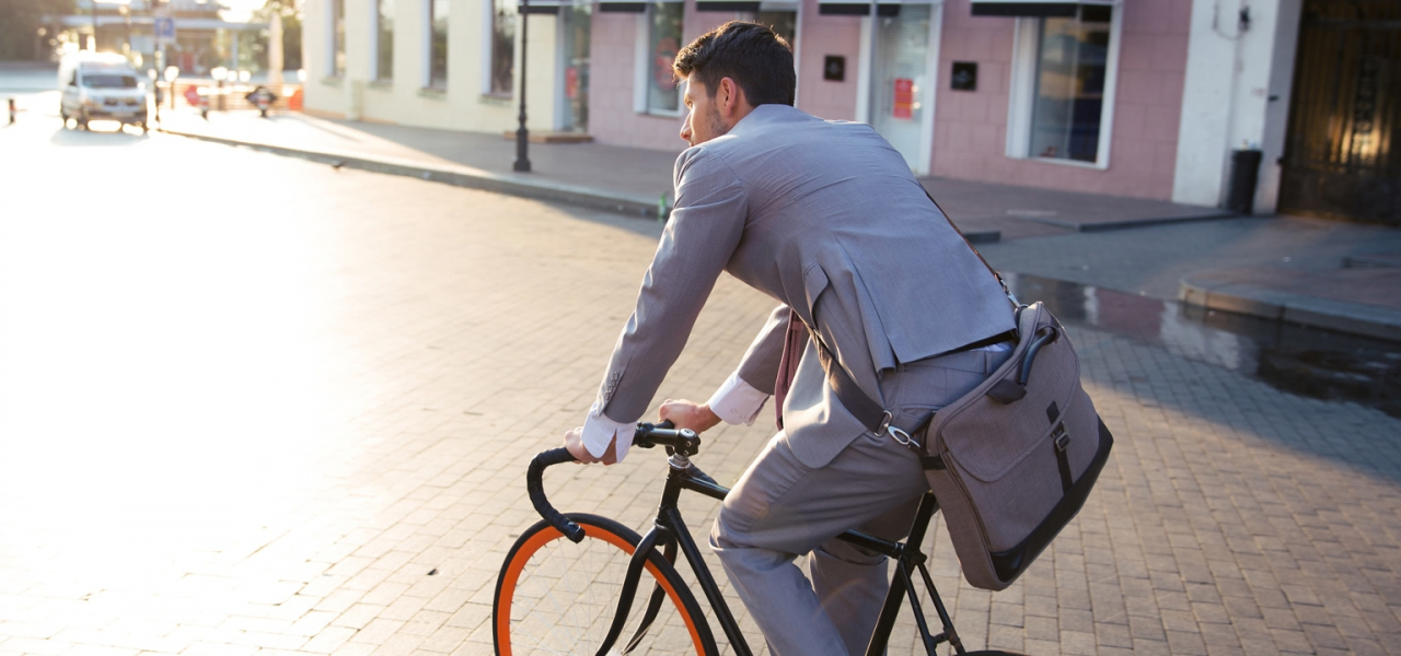 Suited man rides a bike through a town on a sunny day